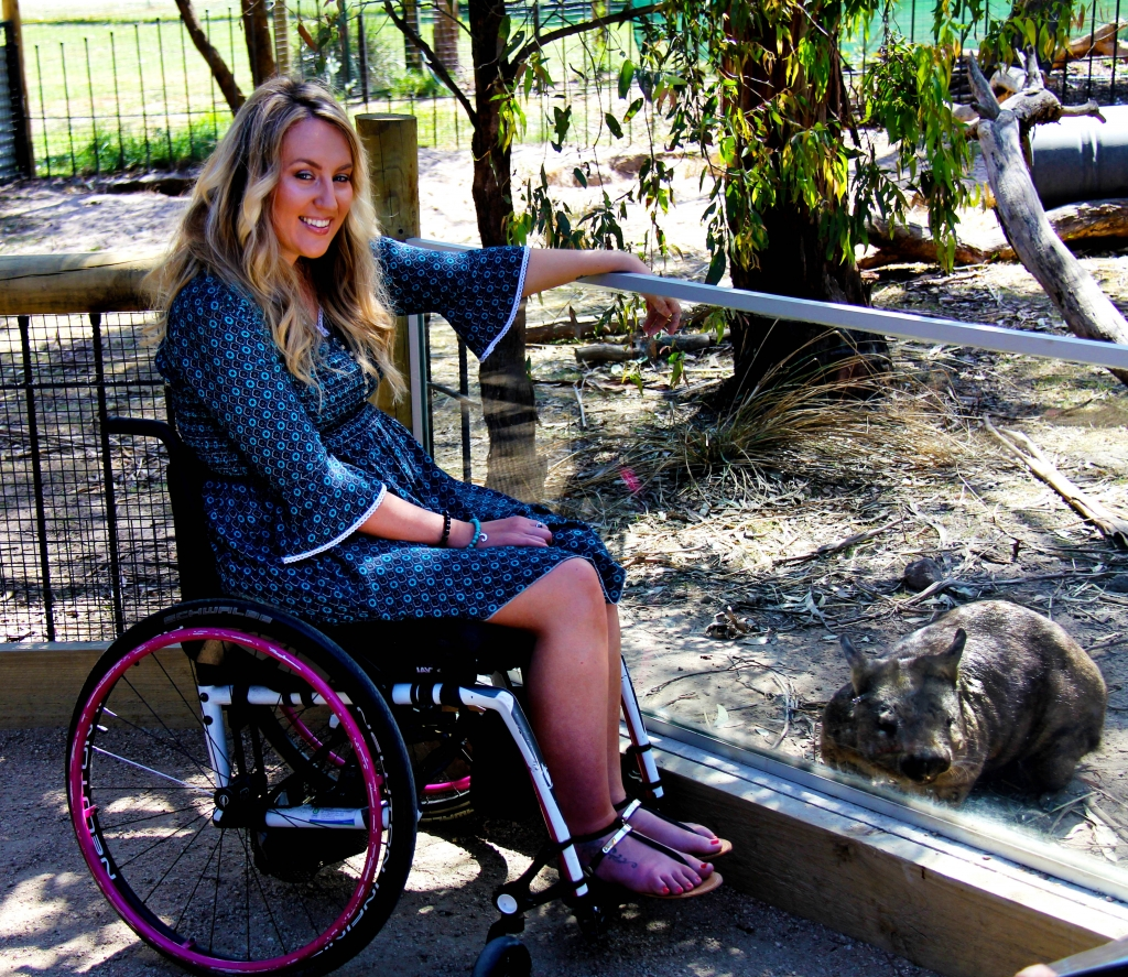 Young woman in wheelchair with wombat at Moonlit Sanctuary Wildlife Conservation Park